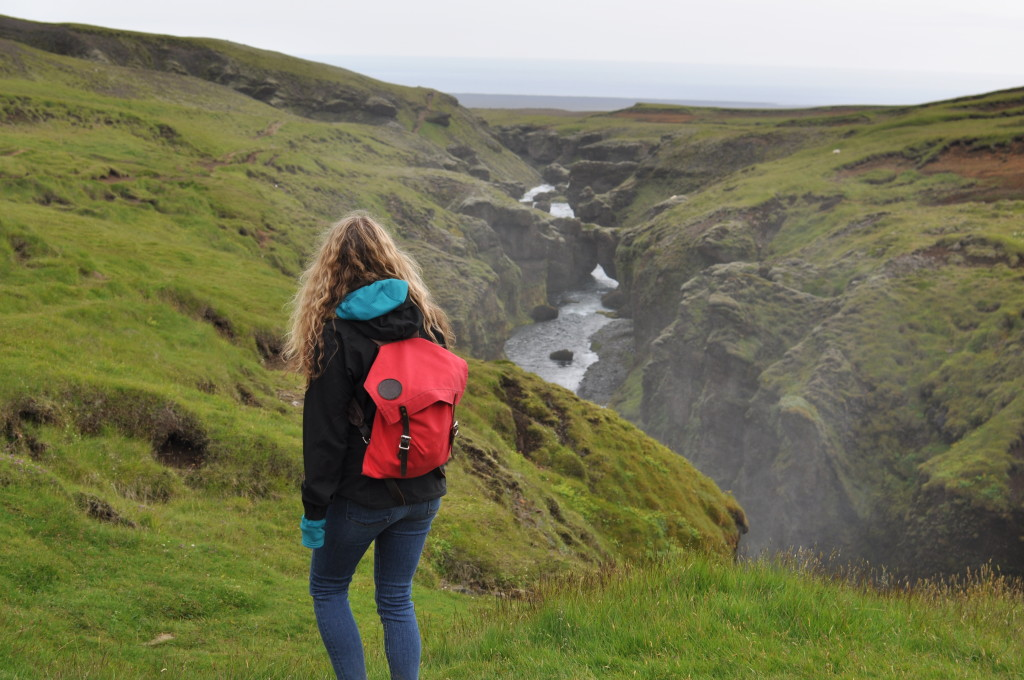 Here is Lily just strolling through magical fairy lands and the impossible home of the Huldufólk above Skógafoss.